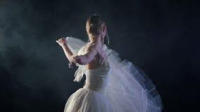 Χαριτωμένο ballerina που χορεύει στο στάδιο Καπνός, ομίχλη, χορευτής μπαλέτου στο άσπρο tutu, κορίτσι στο pointe, περιστροφές γύρ απόθεμα βίντεο