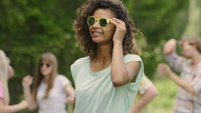 Χαριτωμένο biracial κορίτσι που χορεύει με τους φίλους, νέοι ξένοιαστοι σπουδαστές στο κόμμα λιμνών απόθεμα βίντεο