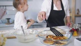 Χαριτωμένο mom με την τηγανίτες λίγων μαγειρεύοντας τυριών εξοχικών σπιτιών κορών Στοκ φωτογραφία με δικαίωμα ελεύθερης χρήσης