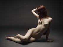 Χαριτωμένο nude κορίτσι συνεδρίασης πέρα από το σκοτεινό υπόβαθρο Στοκ Εικόνα