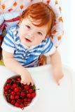 Χαριτωμένο redhead μωρό νηπίων που δοκιμάζει τα γλυκά κεράσια καθμένος στο highchair στην κουζίνα Στοκ Εικόνες