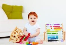 Χαριτωμένο redhead παιχνίδι μωρών με τα ξύλινα παιχνίδια, αριθμοί, που μαθαίνει να μετρά Στοκ Εικόνα