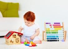 Χαριτωμένο redhead παιχνίδι μωρών με τα ξύλινα παιχνίδια, αριθμοί, που μαθαίνει να μετρά Στοκ εικόνα με δικαίωμα ελεύθερης χρήσης