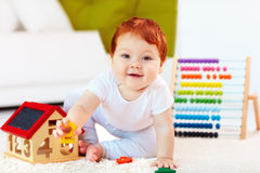 Χαριτωμένο redhead παιχνίδι μωρών με τα ξύλινα παιχνίδια, αριθμοί, που μαθαίνει να μετρά Στοκ Εικόνες