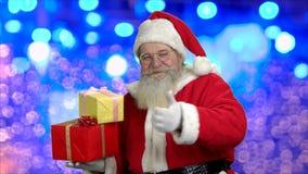 Χαριτωμένο Santa με τα δώρα και τον αντίχειρα επάνω απόθεμα βίντεο