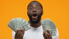 Χαρούμενα δολάρια εκμετάλλευσης νεαρών άνδρων στα χέρια στο φωτεινό υπόβαθρο, επενδύσεις φιλμ μικρού μήκους