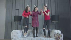 Χαρούμενα θηλυκά στα καπέλα κομμάτων που πηδούν στον καναπέ απόθεμα βίντεο