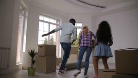 Χαρούμενα οικογενειακά χορεύοντας φέρνοντας κιβώτια στο καινούργιο σπίτι απόθεμα βίντεο