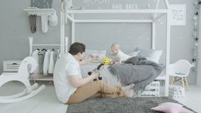 Χαρούμενα παιχνίδια παιχνιδιού μωρών με τον αγαπημένο μπαμπά στο σπίτι απόθεμα βίντεο