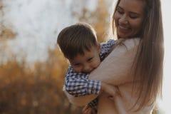 Χαρούμενα χέρια εκμετάλλευσης μητέρων και περιστροφή του γιου της στο δασικό ευτυχές αγόρι που έχει τη διασκέδαση με τη μητέρα το στοκ εικόνες