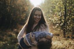 Χαρούμενα χέρια εκμετάλλευσης μητέρων και περιστροφή του γιου της στο δασικό ευτυχές αγόρι που έχει τη διασκέδαση με τη μητέρα το στοκ εικόνα με δικαίωμα ελεύθερης χρήσης