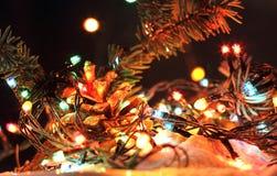 Χαρούμενα Χριστούγεννα, ευτυχή νέα ζωηρόχρωμα φω'τα γιρλαντών ετών στο χιόνι νύχτας Στοκ Φωτογραφίες