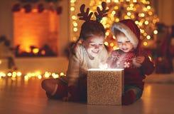 Χαρούμενα Χριστούγεννα! ευτυχή παιδιά με το μαγικό δώρο στο σπίτι Στοκ Εικόνες