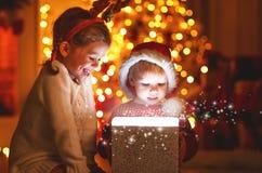 Χαρούμενα Χριστούγεννα! ευτυχή παιδιά με το μαγικό δώρο στο σπίτι Στοκ εικόνα με δικαίωμα ελεύθερης χρήσης