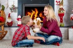 Χαρούμενα Χριστούγεννα και καλές διακοπές! Παιχνίδι μητέρων και γιων με ένα σκυλί παιχνιδιών από την εστία στοκ εικόνες