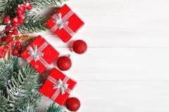 Χαρούμενα Χριστούγεννα και καλή χρονιά Δώρα και fir-tree κλάδοι σε έναν άσπρο ξύλινο πίνακα Εκλεκτική εστίαση Χριστούγεννα στοκ φωτογραφίες
