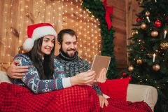 Χαρούμενα Χριστούγεννα και καλή χρονιά Νέες διακοπές εορτασμού ζευγών στο σπίτι Άνδρας και γυναίκα που χρησιμοποιούν ένα PC ταμπλ στοκ φωτογραφία