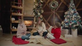 Χαρούμενα Χριστούγεννα και καλή χρονιά Παιδιά Momand που έχουν τη διασκέδαση κοντά στο χριστουγεννιάτικο δέντρο στο εσωτερικό κον απόθεμα βίντεο