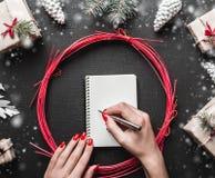 Χαρούμενα Χριστούγεννα και καλή χρονιά Τοπ άποψη των θηλυκών χεριών που γράφουν μια επιστολή Χριστουγέννων Στοκ εικόνα με δικαίωμα ελεύθερης χρήσης