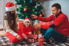 Χαρούμενα Χριστούγεννα και καλή χρονιά Το ευτυχές μικρό κορίτσι κάθεται μεταξύ των γονέων και του γέλιου Η μητέρα κοιτάζει κάτω Φ στοκ εικόνες