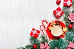 Χαρούμενα Χριστούγεννα και καλή χρονιά Το φλυτζάνι του κακάου, των δώρων και fir-tree διακλαδίζεται σε έναν άσπρο ξύλινο πίνακα Ε στοκ φωτογραφίες