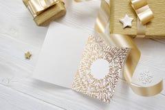 Χαρούμενα Χριστούγεννα κειμένων ευχετήριων καρτών Χριστουγέννων προτύπων με τη χρυσή κορδέλλα δώρων, flatlay σε ένα άσπρο ξύλινο  Στοκ Εικόνες