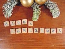 Χαρούμενα Χριστούγεννα που γράφεται στο ξύλο με τη διακόσμηση Στοκ Φωτογραφία