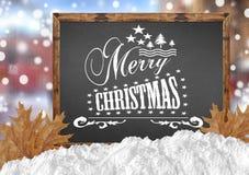 Χαρούμενα Χριστούγεννα στον πίνακα με τα φύλλα και το χιόνι πόλεων Στοκ φωτογραφία με δικαίωμα ελεύθερης χρήσης