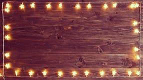 Χαρούμενα Χριστούγεννα! Τα Χριστούγεννα ανάβουν το πλαίσιο στο ξύλινο υπόβαθρο με το διάστημα αντιγράφων στοκ φωτογραφίες