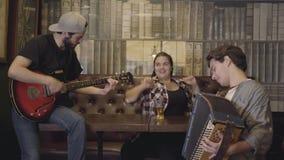 Χαρούμενες νεολαίες που χαμογελούν τη γενειοφόρο κιθάρα παιχνιδιού ανδρών στο φραγμό, το ακκορντέον παιχνιδιού φίλων του ενώ ελκυ απόθεμα βίντεο