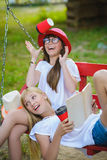 Χαρούμενες φίλες που έχουν τη διασκέδαση στην ταλάντευση υπαίθρια σκοτεινό πορτρέτο δύο πελεκάνων φιλίας έννοιας ανασκόπησης υγρό στοκ εικόνες