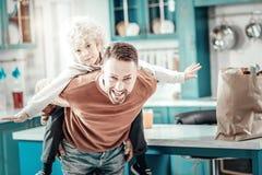 Χαρούμενη αρσενική τοποθέτηση brunette στη κάμερα στην κουζίνα στοκ φωτογραφία με δικαίωμα ελεύθερης χρήσης