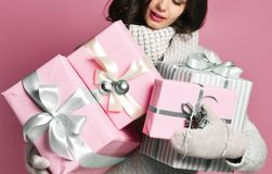 Χαρούμενη γυναίκα που κρατά πολλά κιβώτια με τα δώρα σε ένα ρόδινο υπόβαθρο στοκ εικόνες