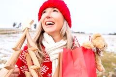 Χαρούμενη γυναίκα που κρατά τις μικρές ξύλινες τσάντες χριστουγεννιάτικων δέντρων και δώρων στοκ φωτογραφίες