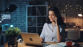 Χαρούμενη γυναίκα που μιλά στο κινητό τηλέφωνο και που εργάζεται με το lap-top στο σκοτεινό γραφείο απόθεμα βίντεο
