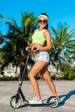 Χαρούμενη γυναίκα που οδηγά ένα μηχανικό δίκυκλο λακτίσματος κοντά στους φοίνικες στην τροπική χώρα Στοκ Φωτογραφία