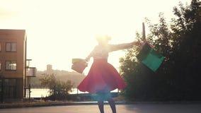 Χαρούμενη γυναίκα Shopaholic στην όμορφη περιστροφή φορεμάτων γύρω από το κράτημα πολλών τσαντών αγορών περπατώντας στην οδό μέσω φιλμ μικρού μήκους