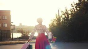 Χαρούμενη γυναίκα Shopaholic στο όμορφο φόρεμα που κρατά πολλές τσάντες αγορών περπατώντας στην οδό μέσω του ήλιου κατά τη διάρκε απόθεμα βίντεο