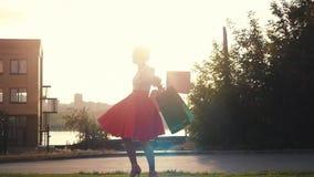 Χαρούμενη γυναίκα Shopaholic στο όμορφο φόρεμα που κρατά πολλές τσάντες αγορών περπατώντας στην οδό μέσω του ήλιου κατά τη διάρκε φιλμ μικρού μήκους