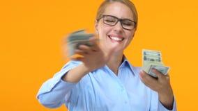 Χαρούμενη επιχειρησιακή γυναίκα που ρίχνει τα μετρητά δολαρίων, επιτυχής κερδοφόρα διαπραγμάτευση, πλούτος φιλμ μικρού μήκους