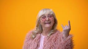 Χαρούμενη ηλικιωμένη κυρία στα αστεία ρόδινα ενδύματα που κάνει rocker τη χειρονομία, positiveness απόθεμα βίντεο