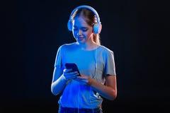 Χαρούμενη θετική γυναίκα που επιλέγει ένα τραγούδι Στοκ εικόνες με δικαίωμα ελεύθερης χρήσης