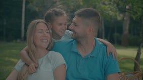 Χαρούμενη κόρη που αγκαλιάζει τους χαμογελώντας γονείς υπαίθρια φιλμ μικρού μήκους