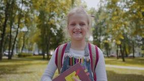 Χαρούμενη μαθήτρια με το σακίδιο πλάτης που κρατά ένα βιβλίο μένοντας στο σχολικό ναυπηγείο Πορτρέτο ενός αρκετά έξυπνου χαμόγελο απόθεμα βίντεο