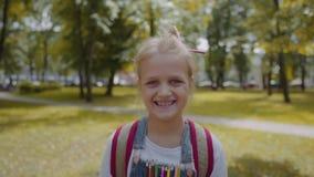 Χαρούμενη μαθήτρια με το σακίδιο πλάτης που κρατά ένα βιβλίο μένοντας στο σχολικό ναυπηγείο Πορτρέτο ενός αρκετά έξυπνου χαμόγελο φιλμ μικρού μήκους