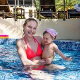 Χαρούμενη μητέρα με λίγη κόρη που λούζει στη λίμνη στοκ εικόνες