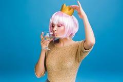 Χαρούμενη νέα γυναίκα πορτρέτου με τη ρόδινη σαμπάνια κατανάλωσης κουρέματος με κλειστός στο μπλε υπόβαθρο Brightful makeup με στοκ εικόνες