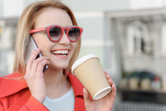 Χαρούμενη νέα γυναίκα που απολαμβάνει την ανακοίνωση σχετικά με το smartphone Στοκ Φωτογραφίες