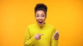 Χαρούμενη νέα γυναίκα που δείχνει στο smartphone υπό εξέταση, σε απευθείας  στοκ φωτογραφίες