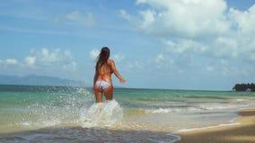 Χαρούμενη νέα λεπτή γυναίκα στο μπικίνι που τρέχει κατά μήκος της εξωτικής άσπρης αμμώδους παραλίας μέσω του καταβρέχοντας νερού  φιλμ μικρού μήκους